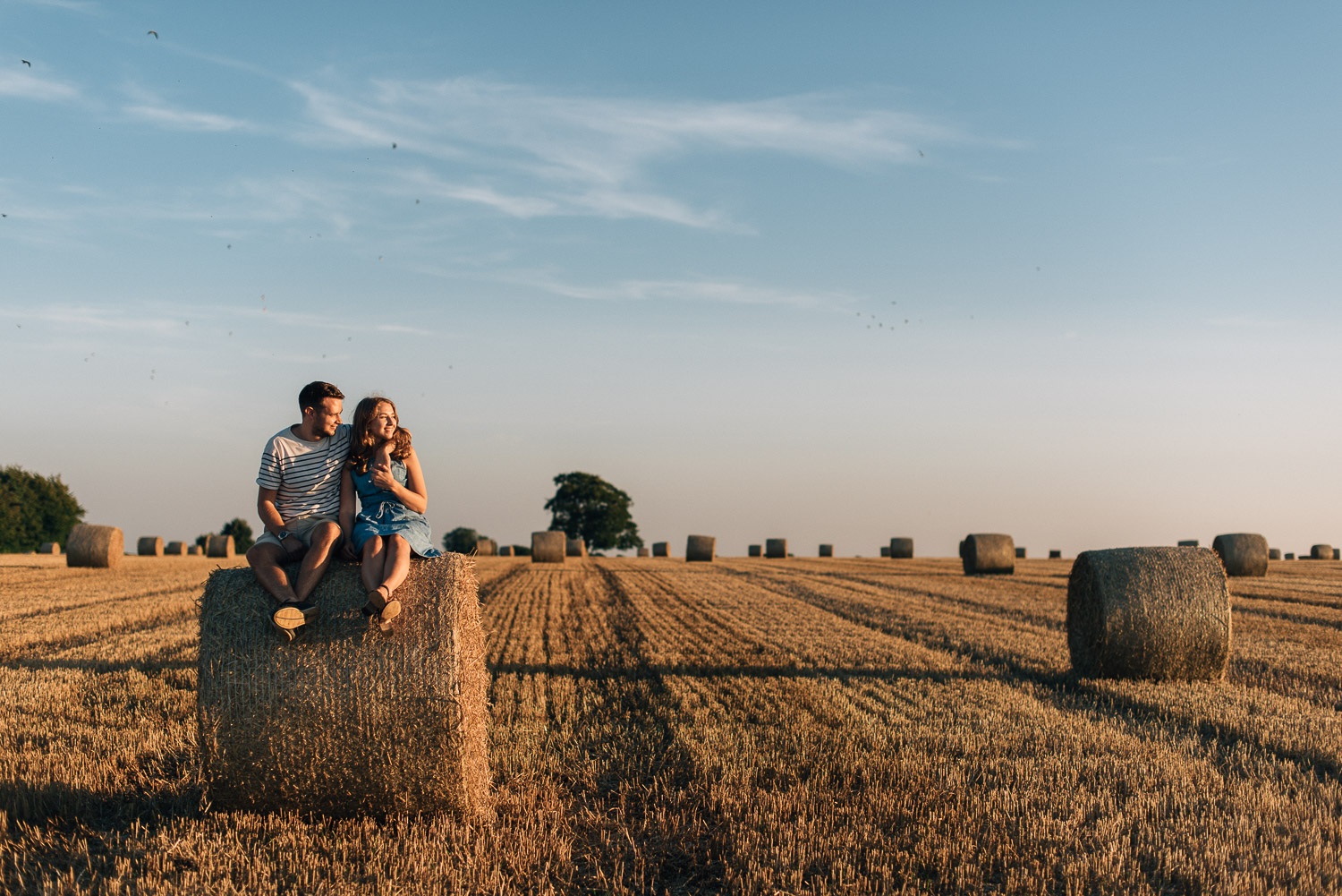 couple sitting on hay bales in sunset by alternative london wedding photographer the shannons photography