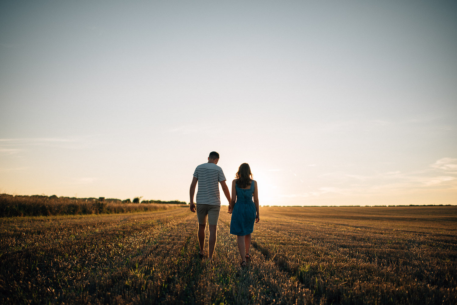 couple walking into sunset in cotswolds by alternative london wedding photographer the shannons photography