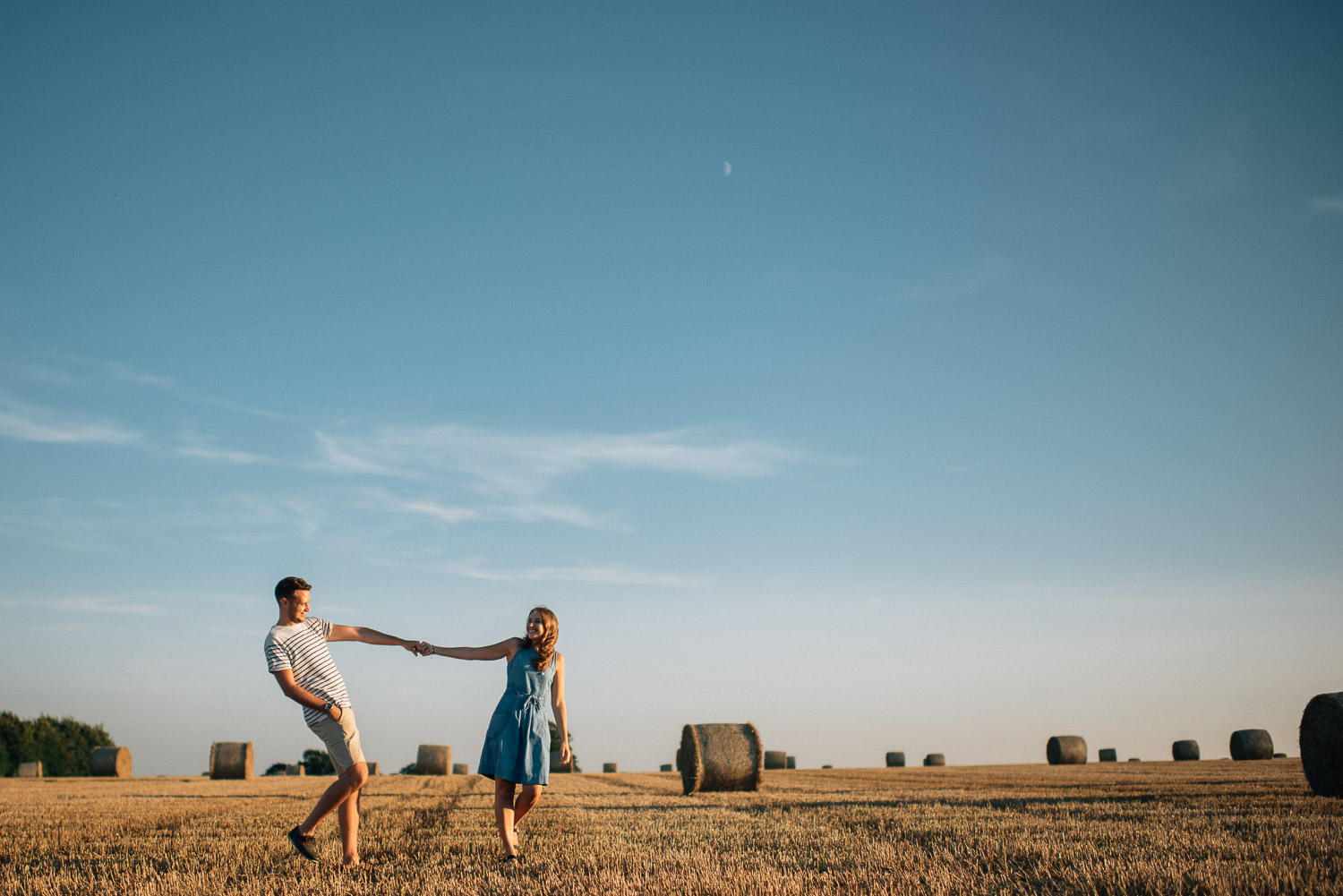 couple holding hands in field by alternative london wedding photographer the shannons photography