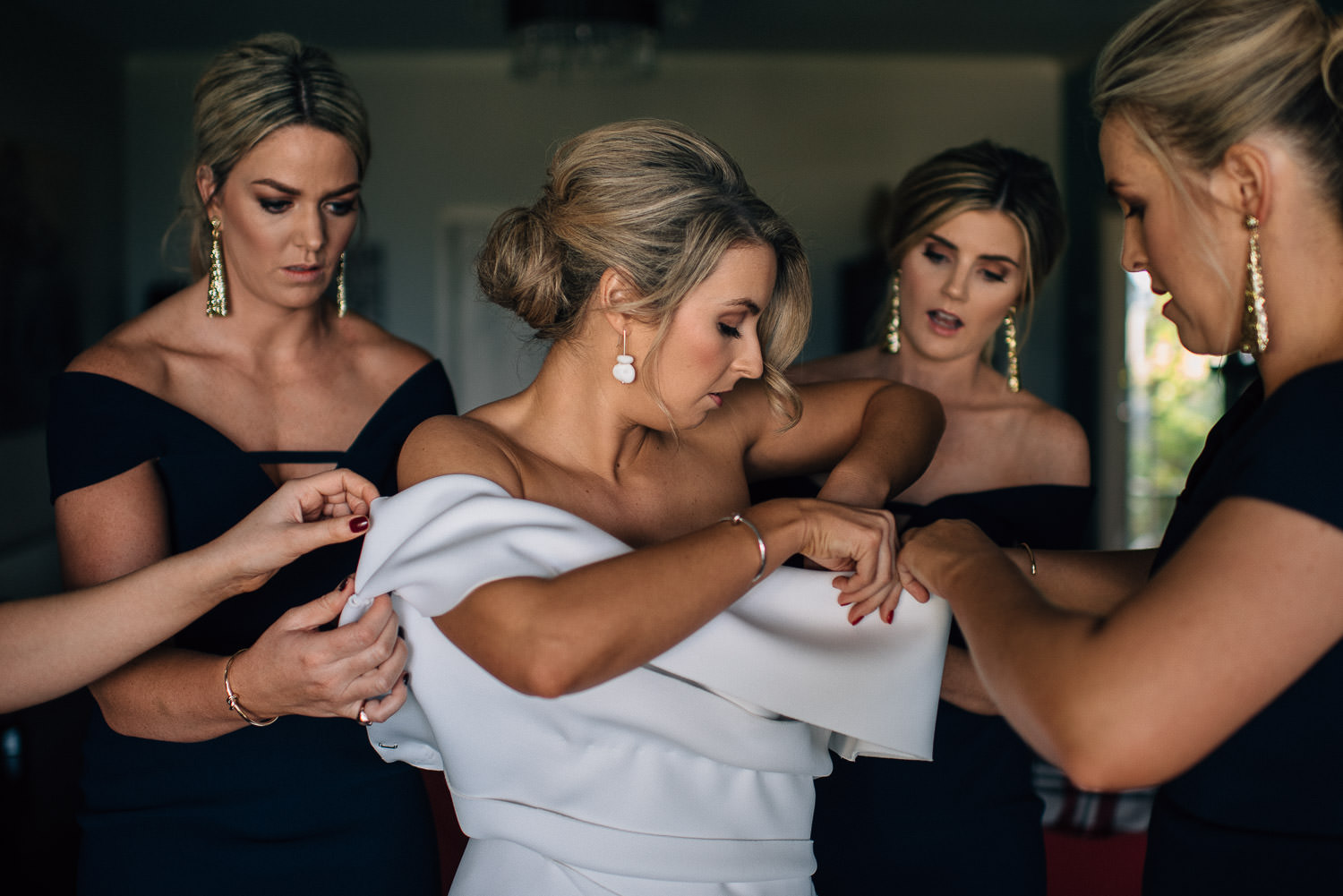bride putting on wedding dress in yarra valley by creative and alternative destination wedding photographer the shannons photography