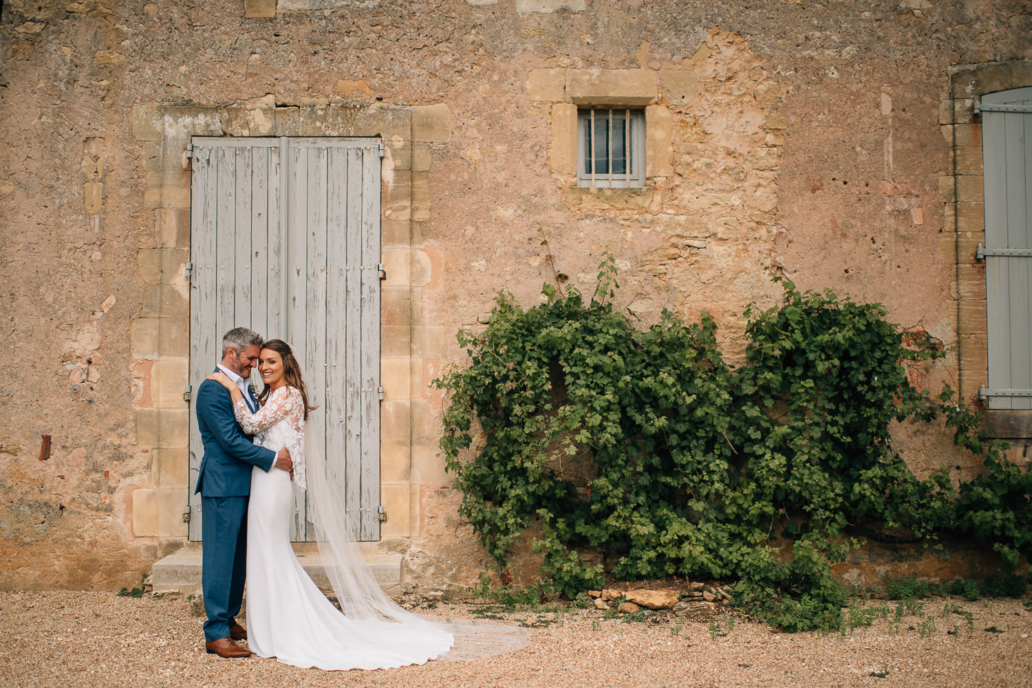 Bride and groom embrace infront of chateau de la bourlie wedding by french destination wedding photographer the shannons photography