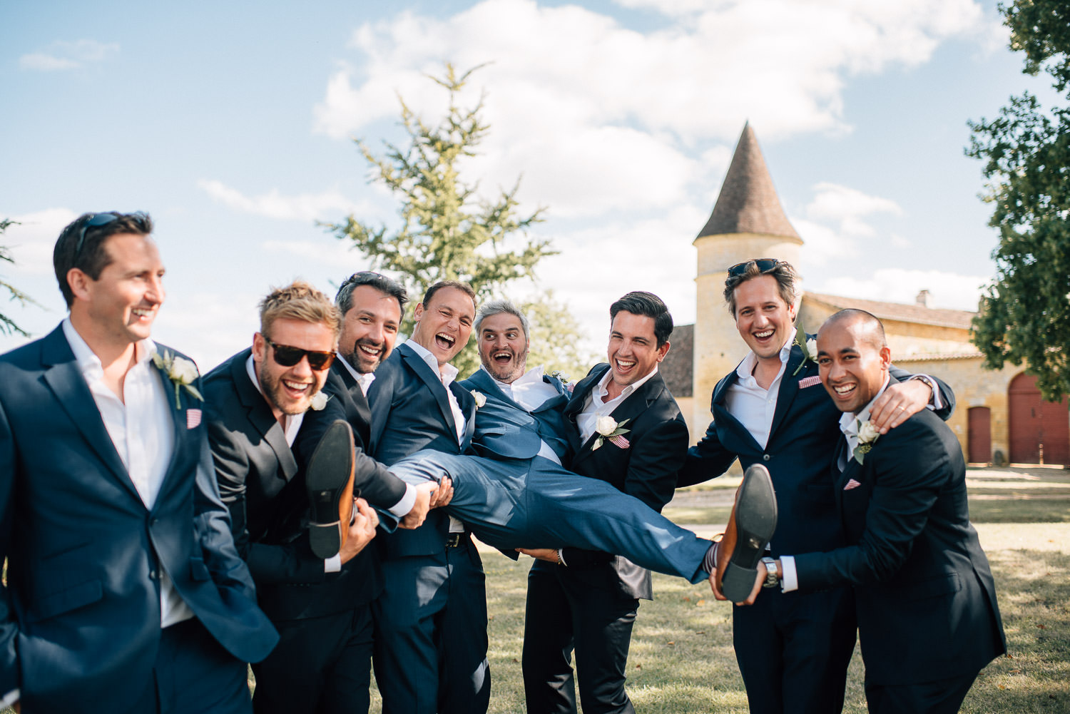 Groomsmen laughing in chateau de la bourlie wedding by destination wedding photographer the shannons photography