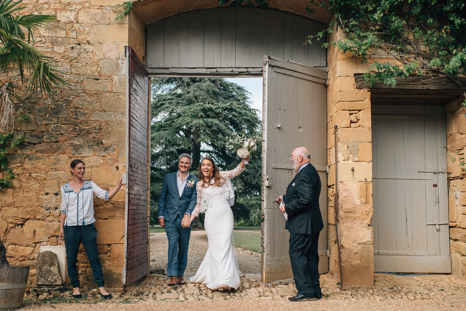 Bride and groom enter into courtyard in chateau de la bourlie wedding by french destination wedding photographer the shannons photography
