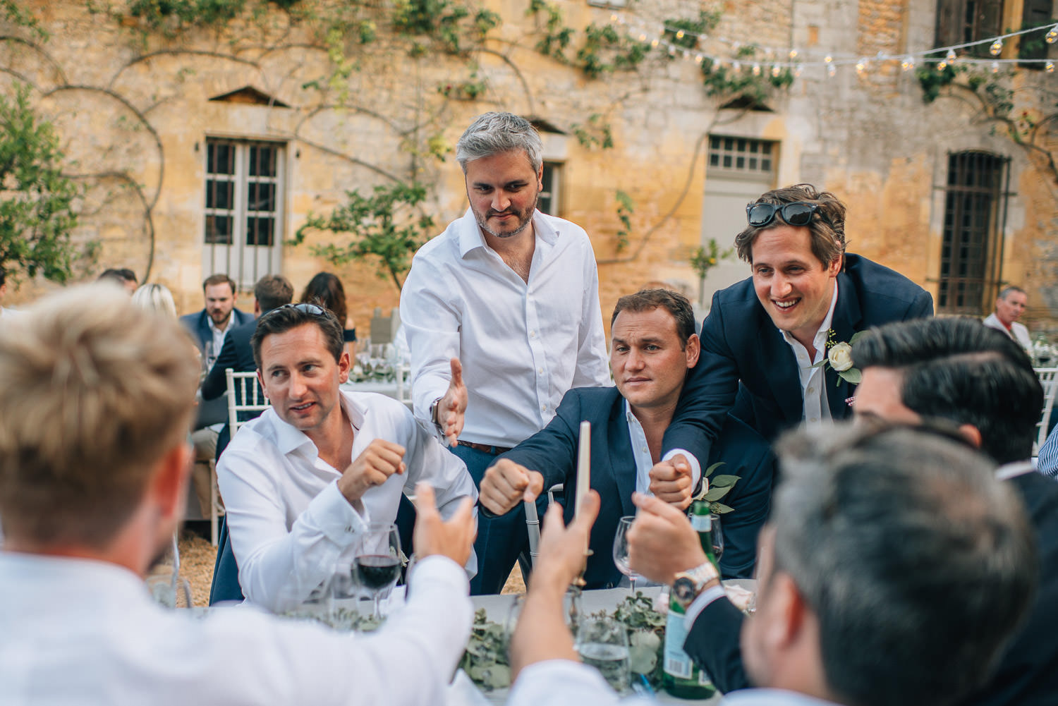 Groom with guests in courtyard in chateau de la bourlie wedding by french destination wedding photographer the shannons photography