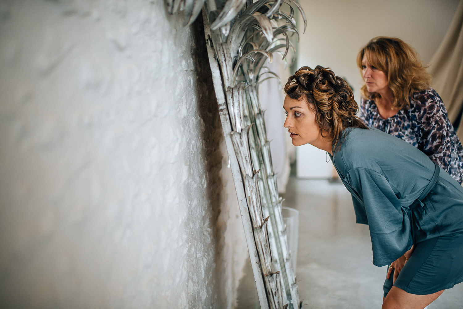 Bride looking into mirror in Chateau de la Bourlie Wedding by creative and alternative destination wedding photographer the shannons photography