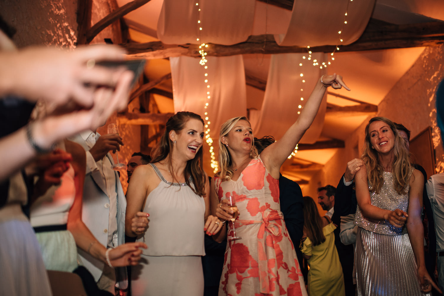 Guests dancing in stables in chateau de la bourlie wedding by french destination wedding photographer the shannons photography