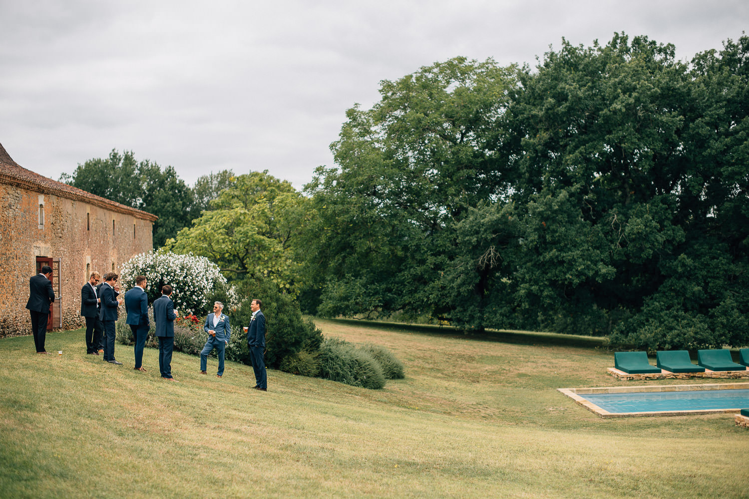 Groomsmen next to stables in Chateau de la Bourlie Wedding by creative and alternative destination wedding photographer the shannons photography