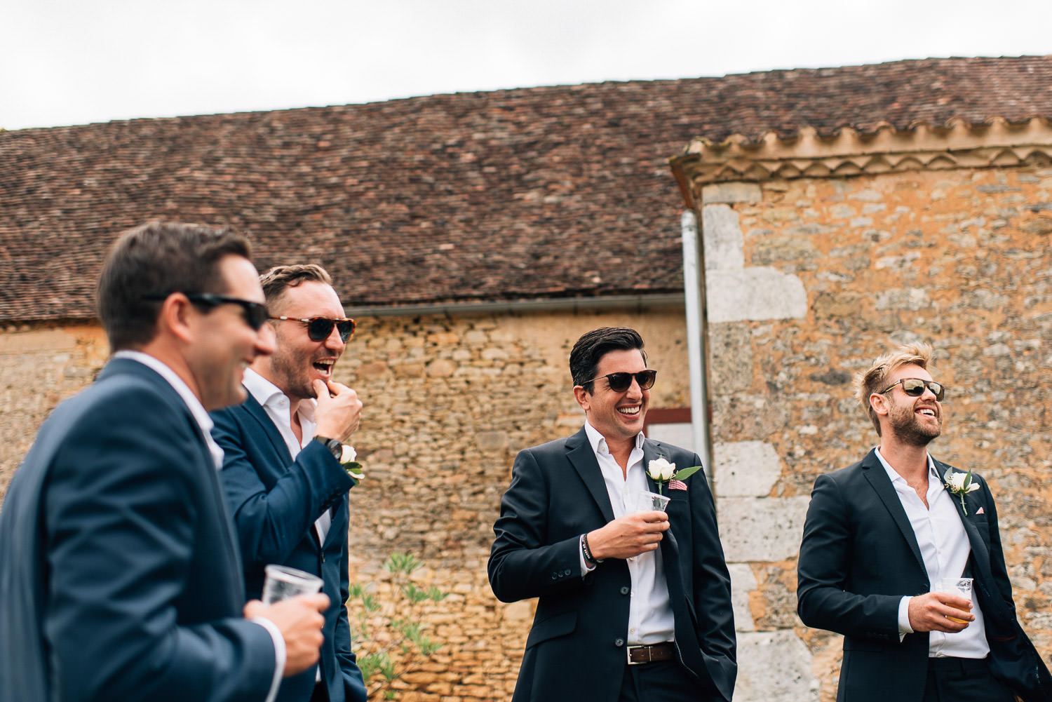 Groomsmen laughing in Chateau de la Bourlie Wedding by creative and alternative destination wedding photographer the shannons photography