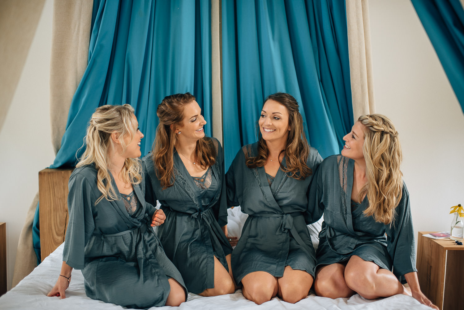 Bridesmaids sitting on bed in Chateau de la Bourlie Wedding by creative and alternative destination wedding photographer the shannons photography