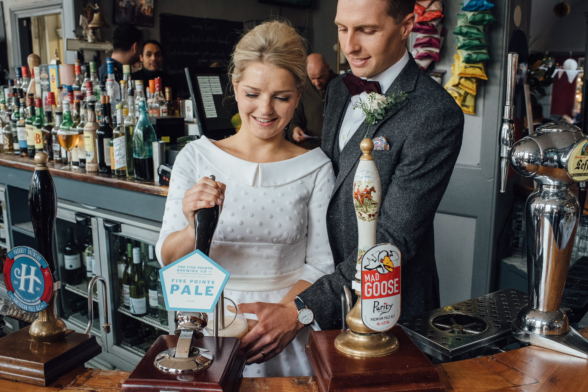 Bride pulling pint in the londesborough pub in stoke newington town hall wedding by creative and alternative london wedding photographer the shannons photography