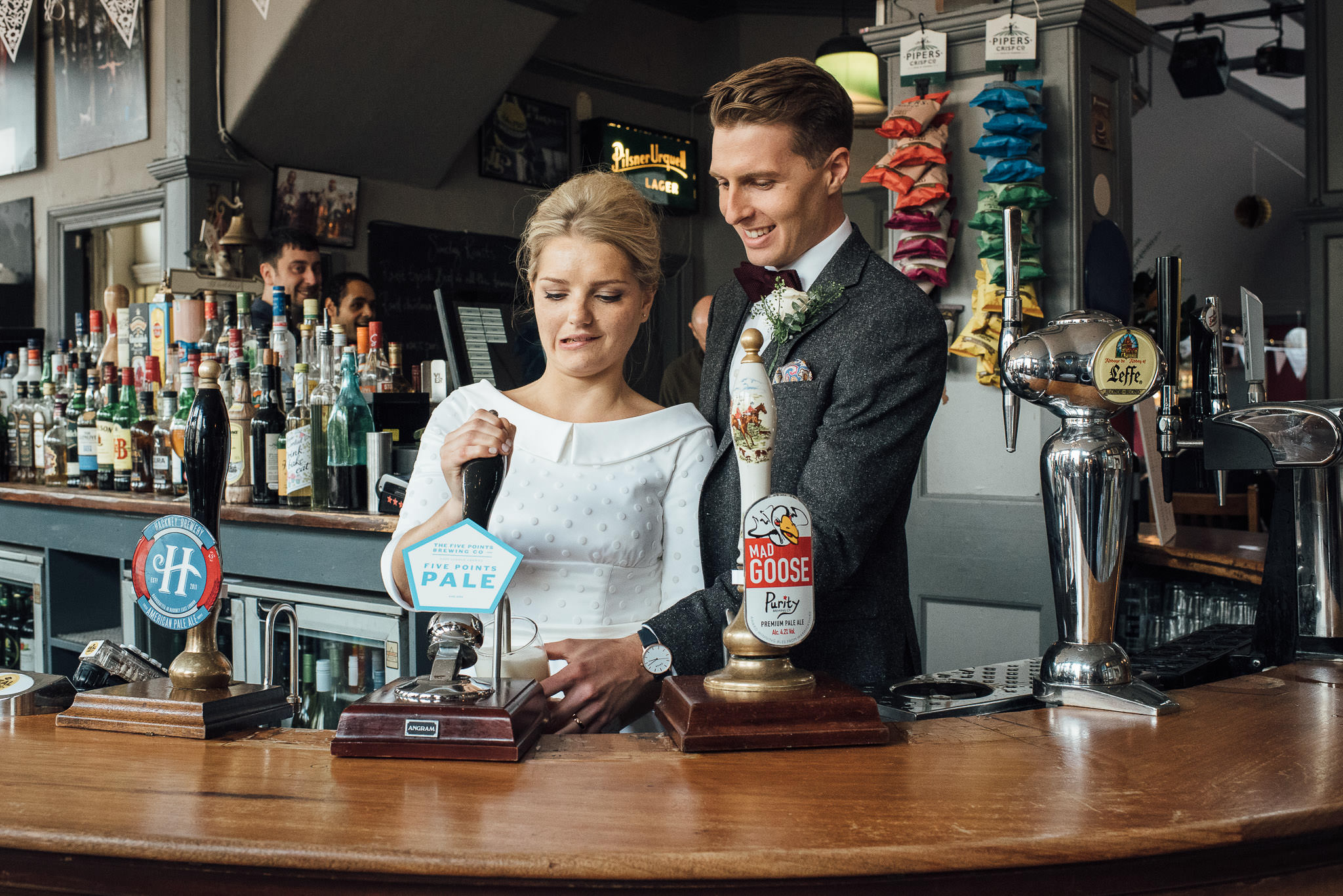 Groom pulling pint in the londesborough pub in stoke newington town hall wedding by creative and alternative london wedding photographer the shannons photography