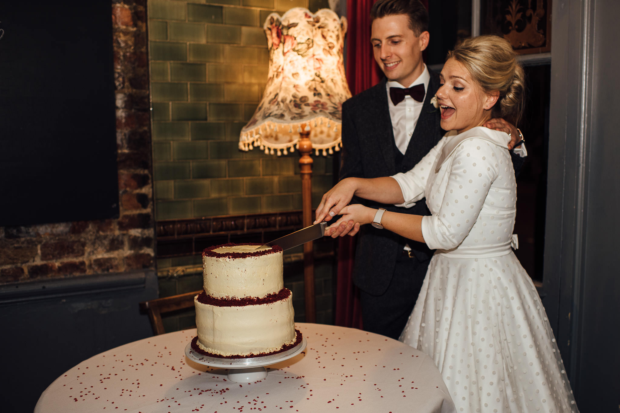 Cutting ooh lou lou vegan wedding cake in stoke newington town hall wedding by creative and alternative london wedding photographer the shannons photography