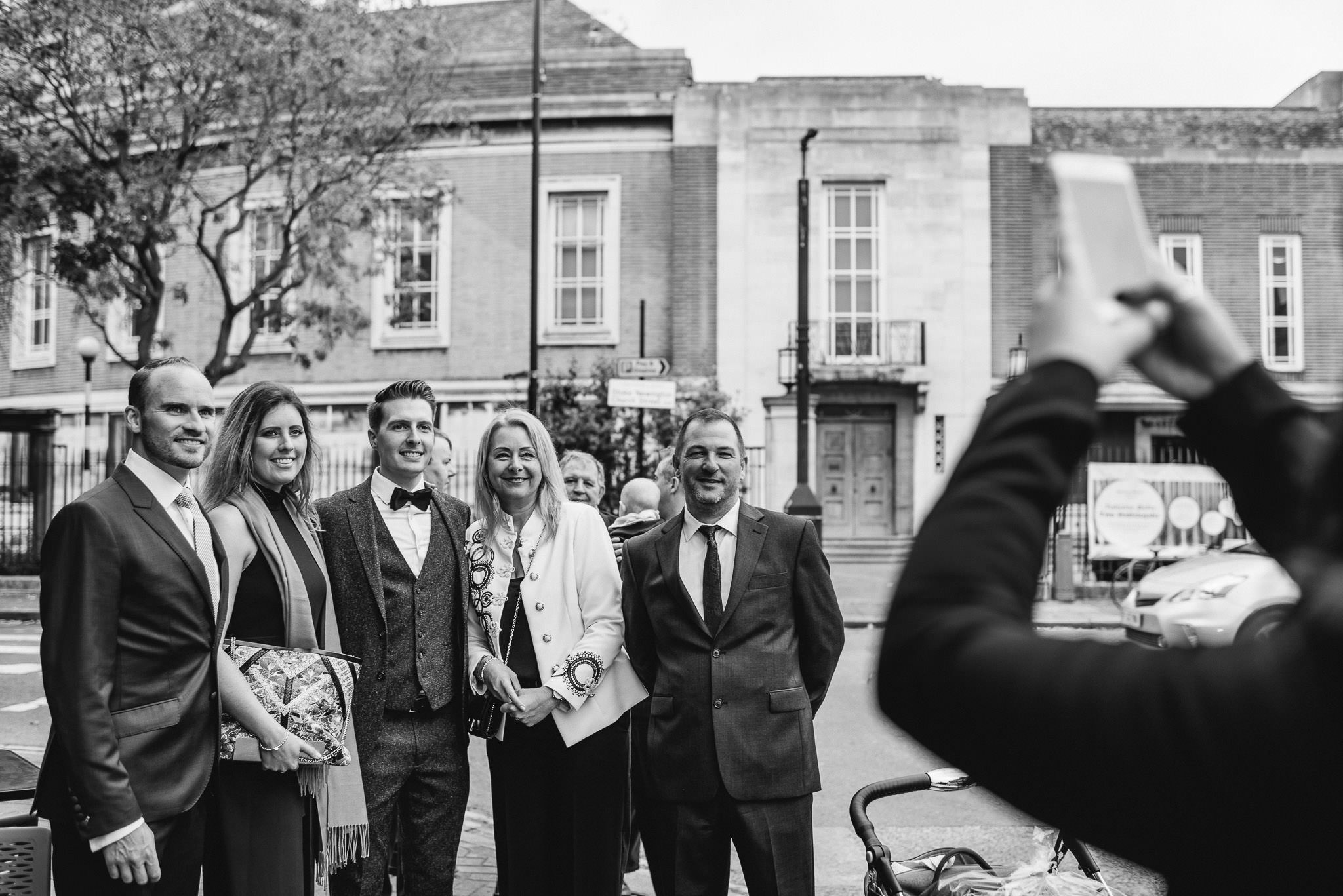 Guests outside rose and crown pub stoke newington in stoke newington town hall wedding by creative and alternative london wedding photographer the shannons photography