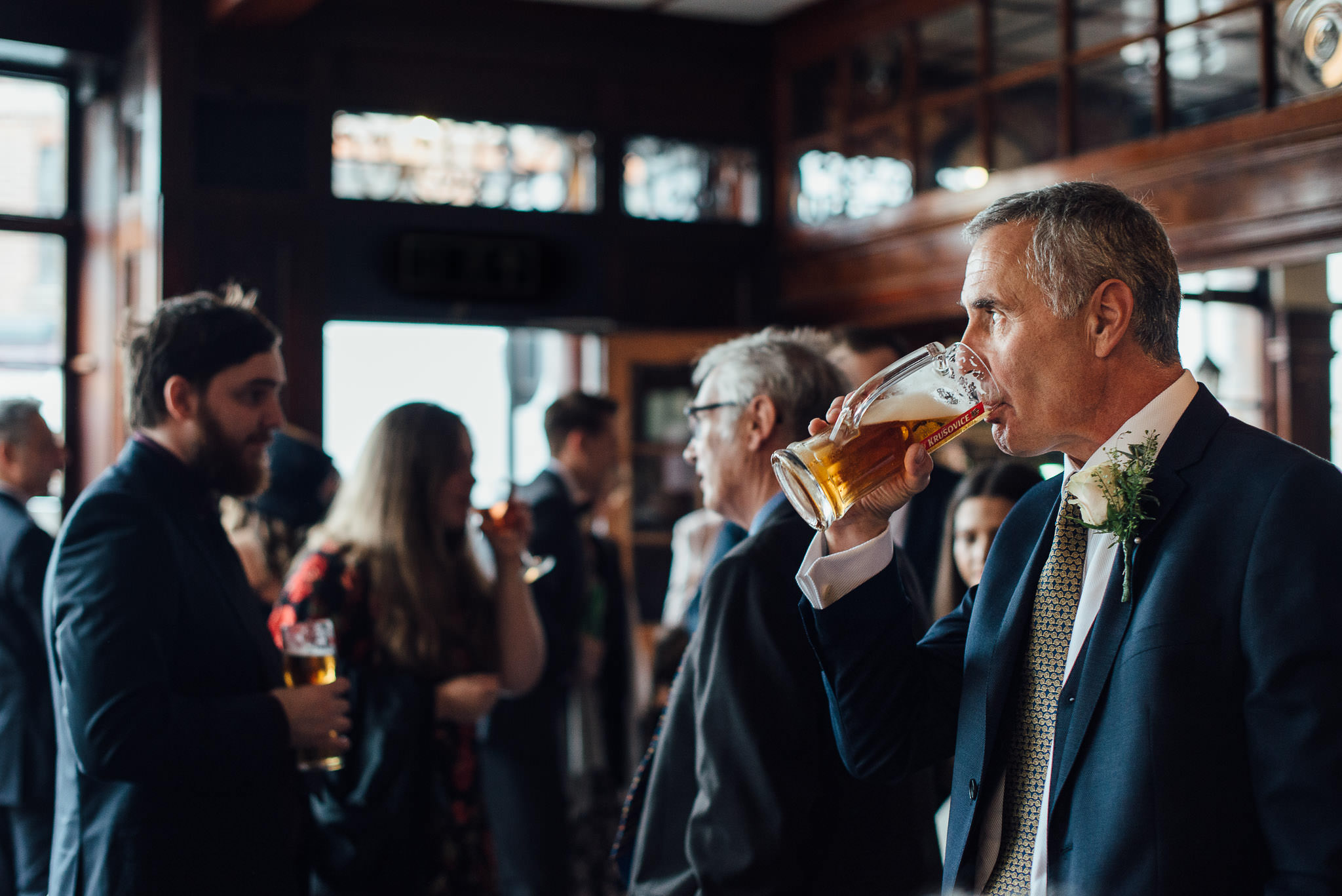 Guests drinking in the rose and crown pub in stoke newington town hall wedding by creative and alternative london wedding photographer the shannons photography