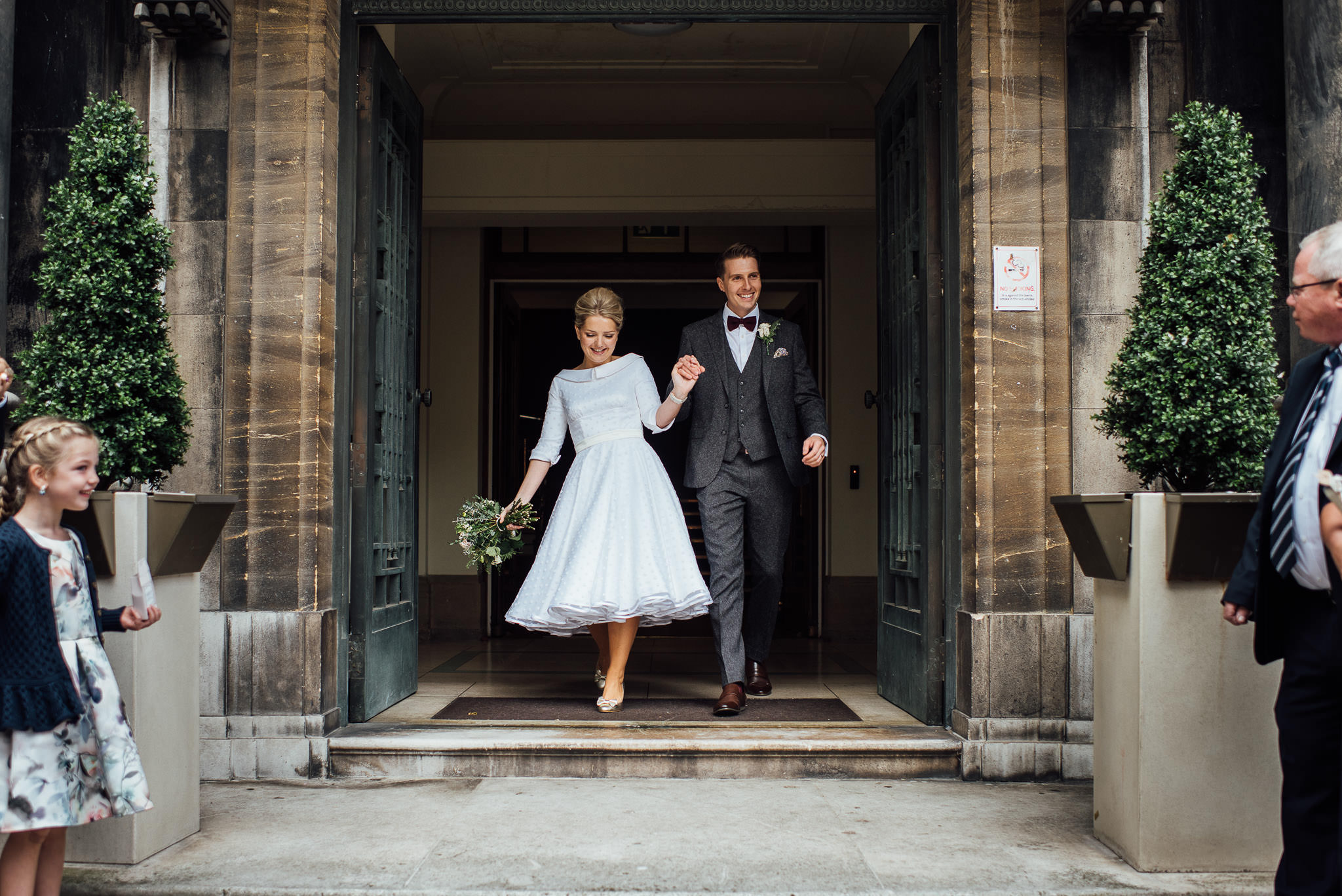 Couple exiting stoke newington town hall in stoke newington town hall wedding by creative and alternative london wedding photographer the shannons photography
