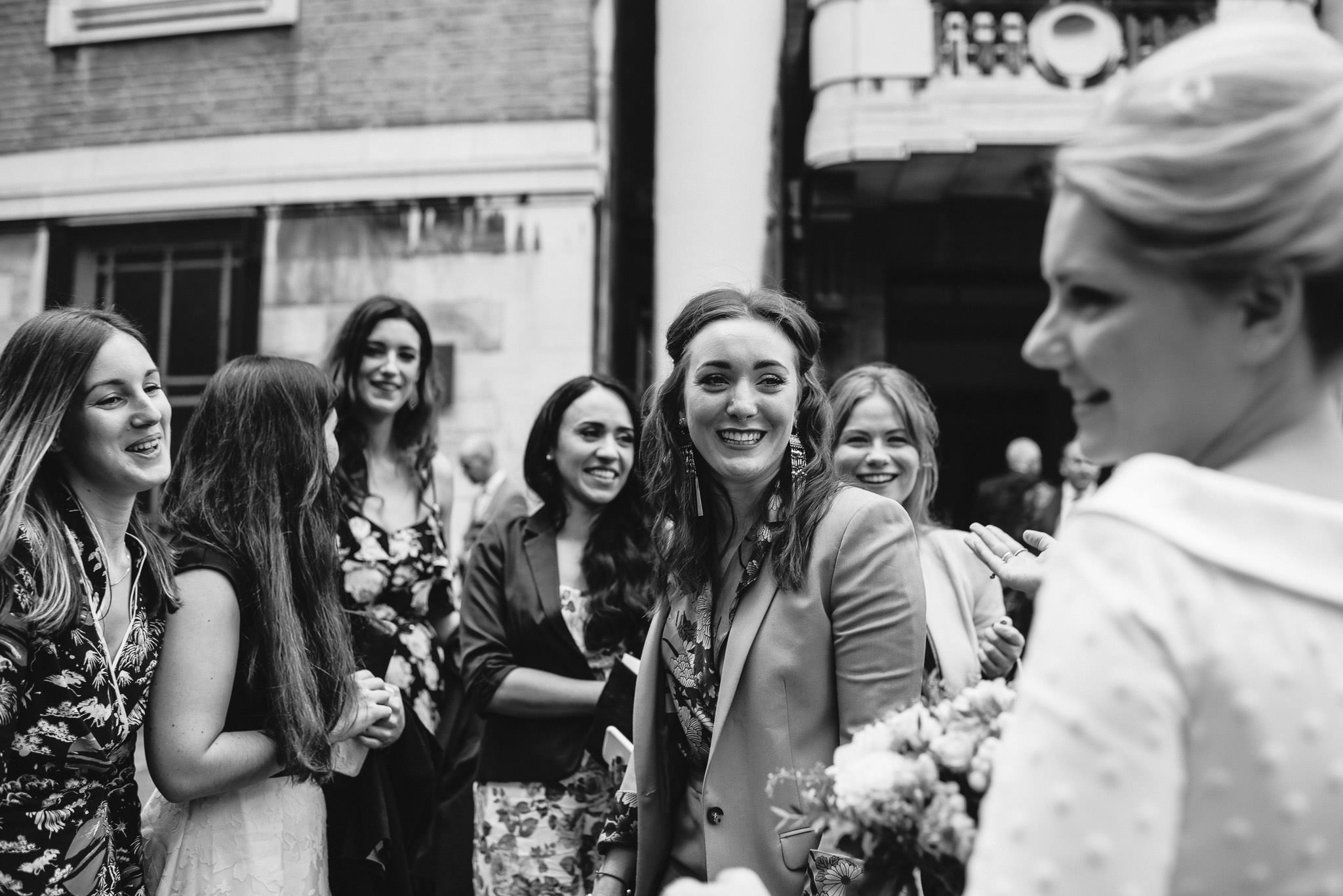 Bride and friends outside town hall in stoke newington town hall wedding by creative and alternative london wedding photographer the shannons photography