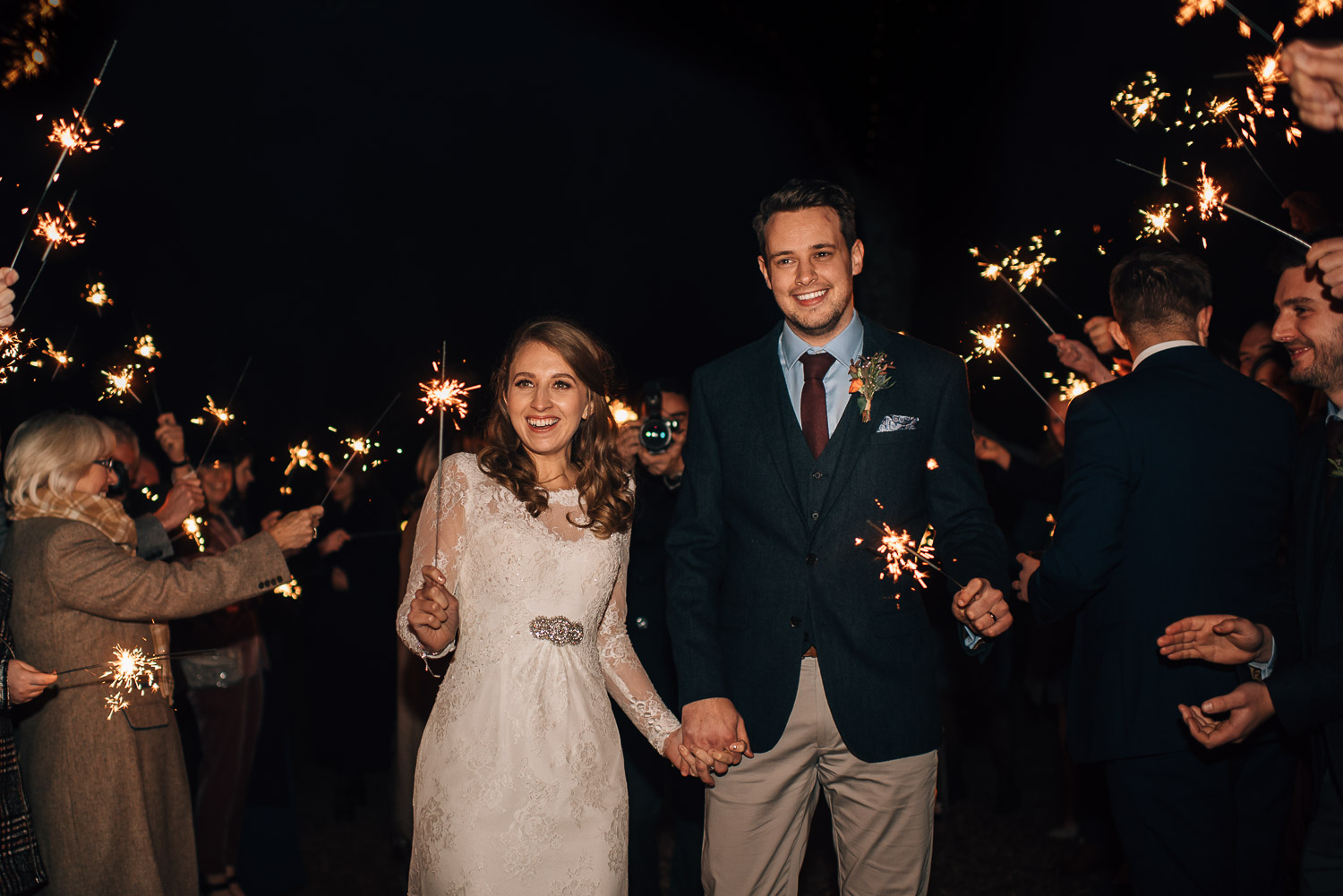bride and groom holding sparklers by creative and alternative london wedding photographer the shannons photography