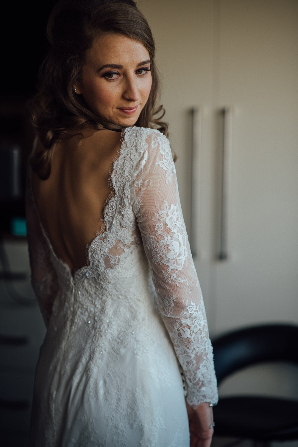 bride looking at herself in the mirror by creative and alternative london wedding photographer the shannons photography