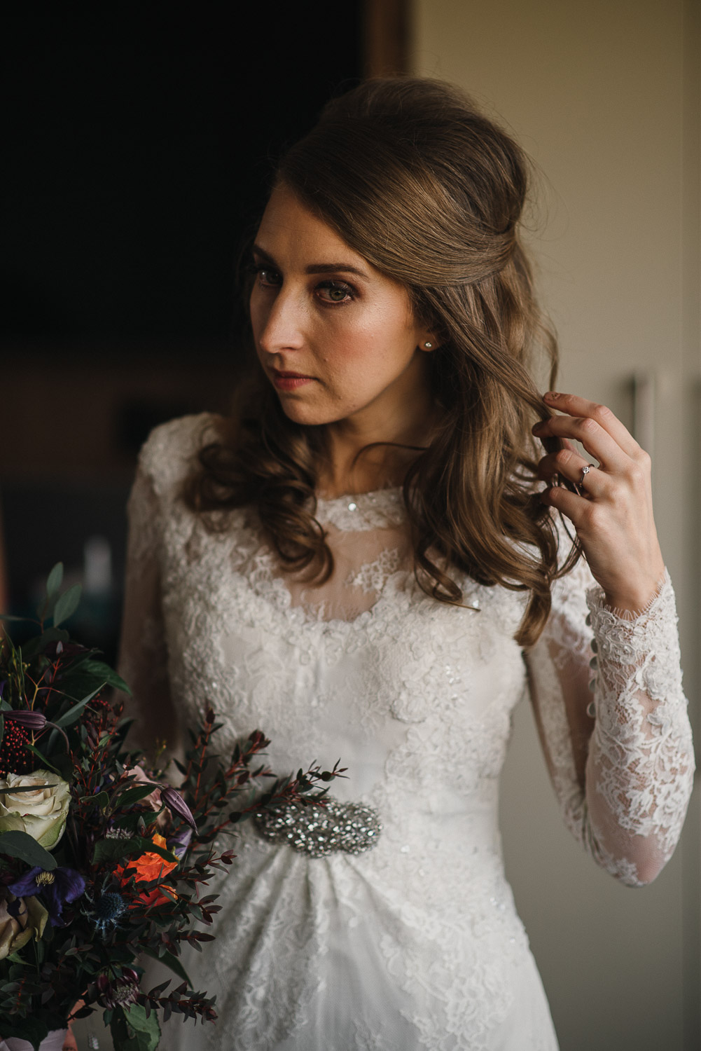 bride doing her hair by creative and alternative london wedding photographer the shannons photography