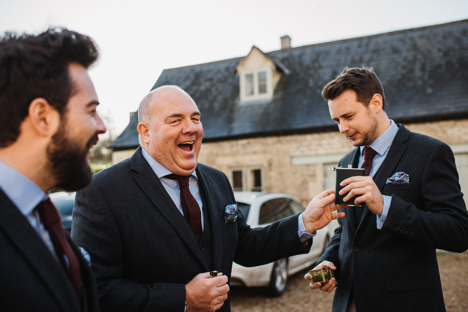 groom laughing at cripps barn by creative and alternative london wedding photographer the shannons photography