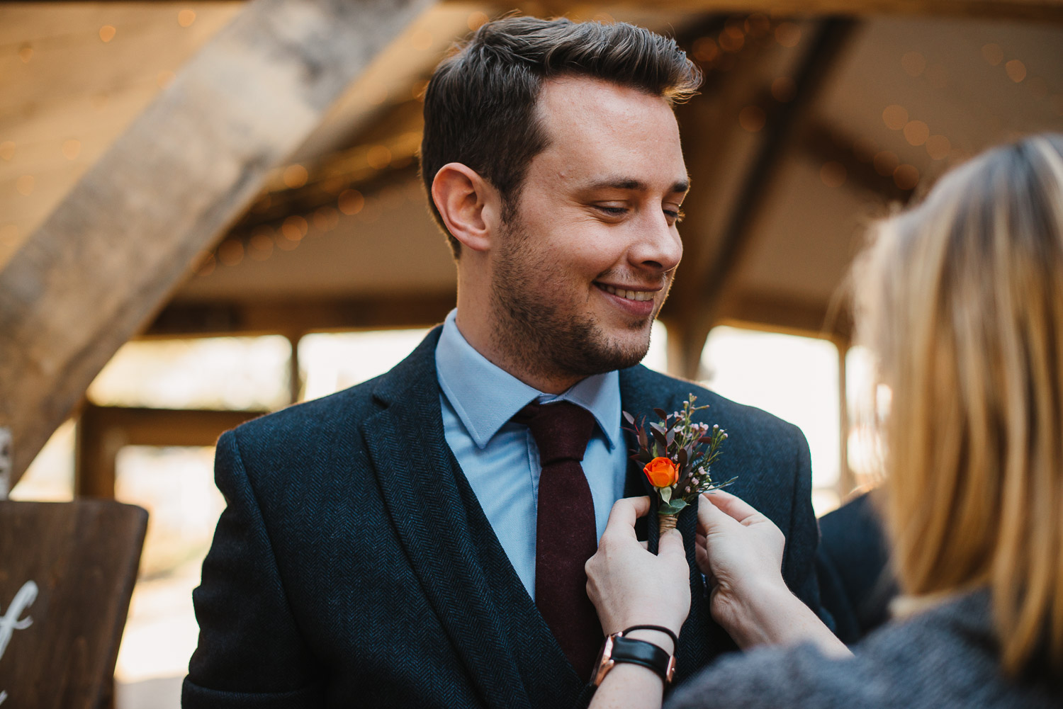 groom doing his button hold at cripps barn by creative and alternative london wedding photographer the shannons photography