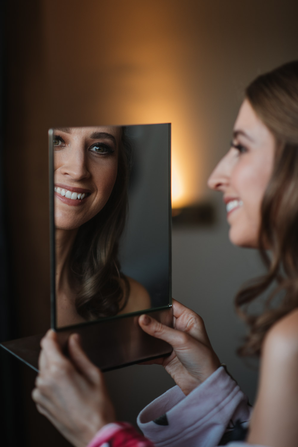 bride smiling with the mirror by creative and alternative london wedding photographer the shannons photography