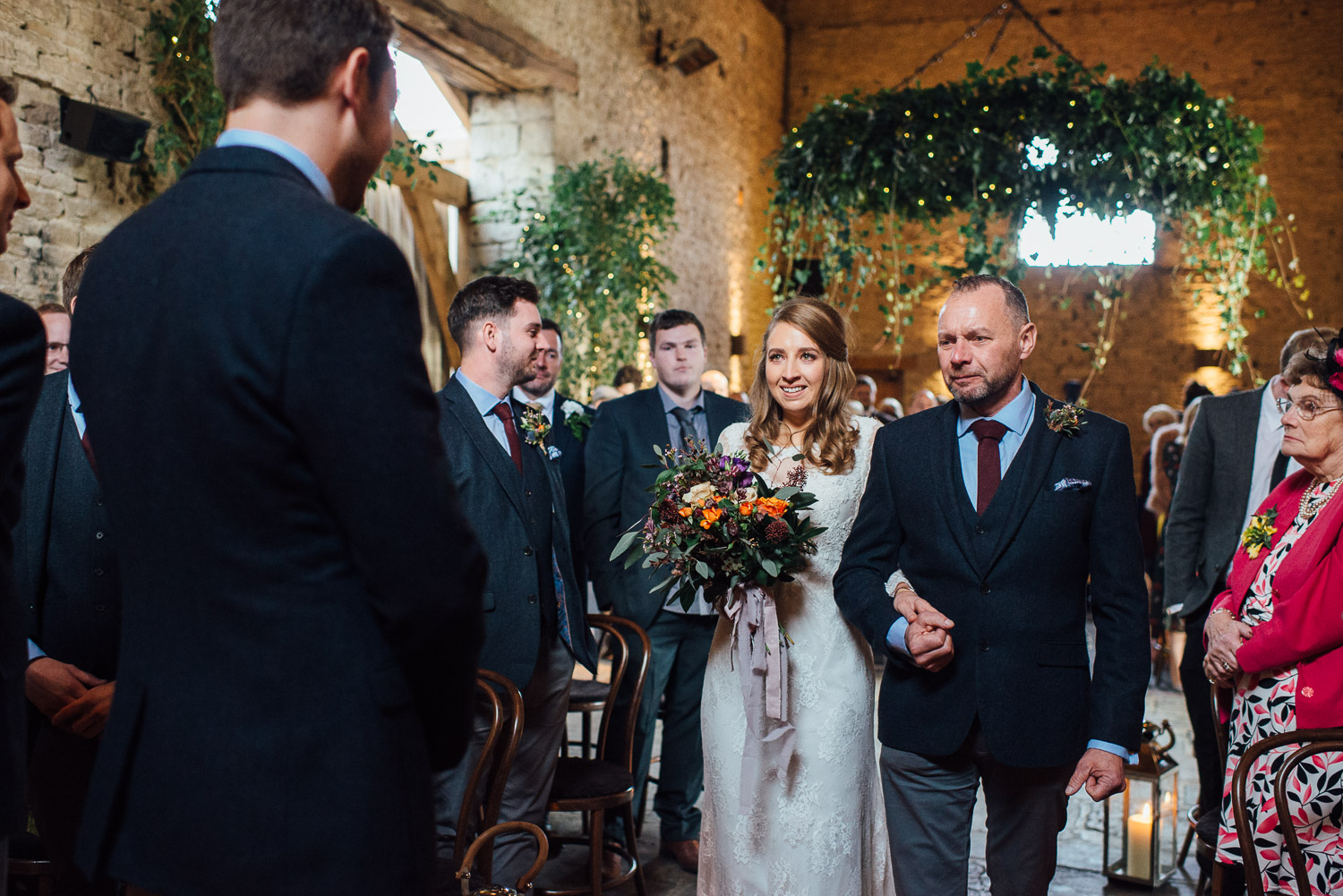 bride smiling as she walks down the aisle by creative and alternative london wedding photographer the shannons photography