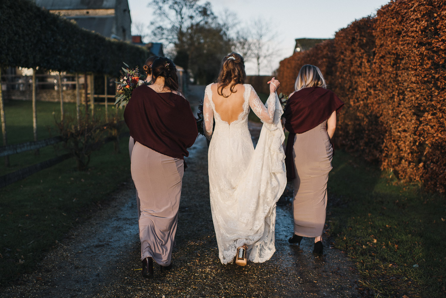 bride walking with bridesmaids at cripps barn by creative and alternative london wedding photographer the shannons photography