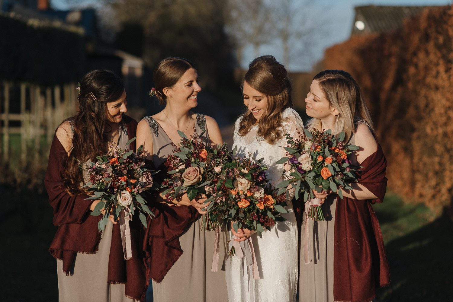 bridesmaids holding large bouquets at cripps barn by creative and alternative london wedding photographer the shannons photography