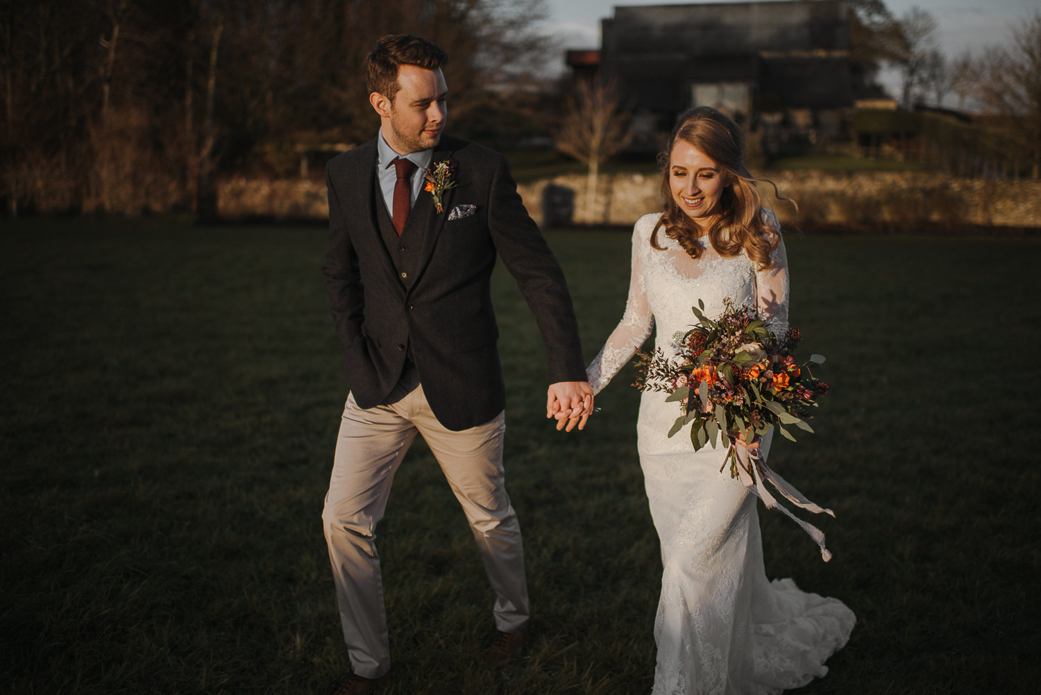 groom smiling at bride at cripps barn by creative and alternative london wedding photographer the shannons photography