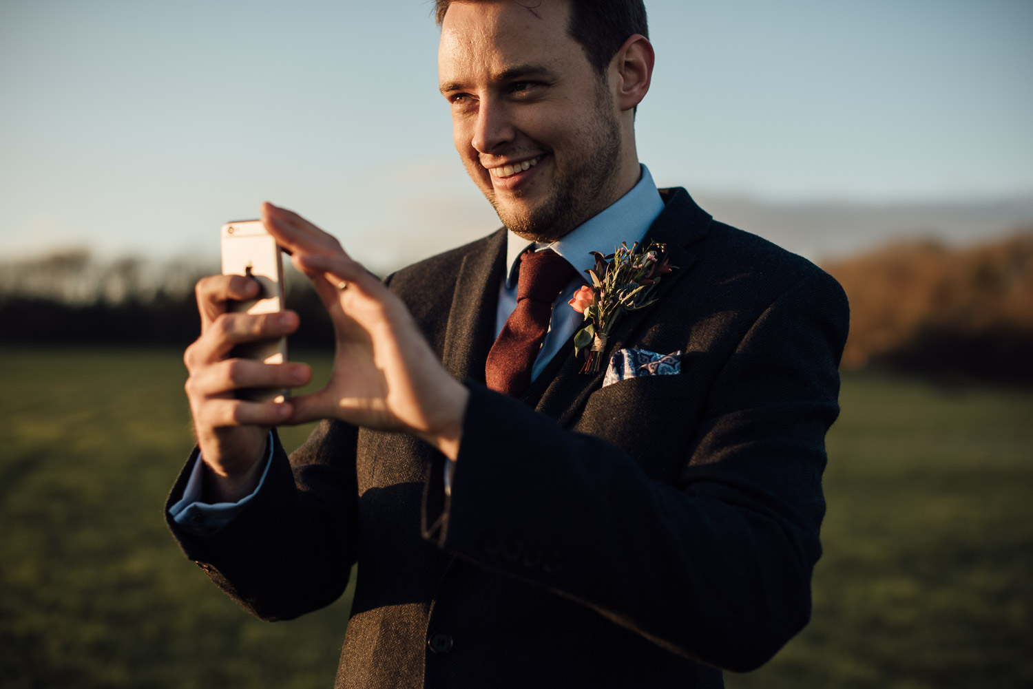 groom laughing at sunset by creative and alternative london wedding photographer the shannons photography