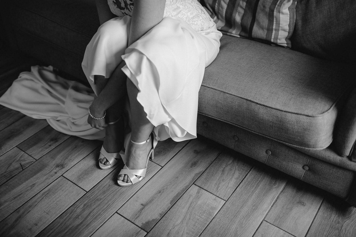 bride putting on wedding shoes by bath wedding photographer the shannons photography