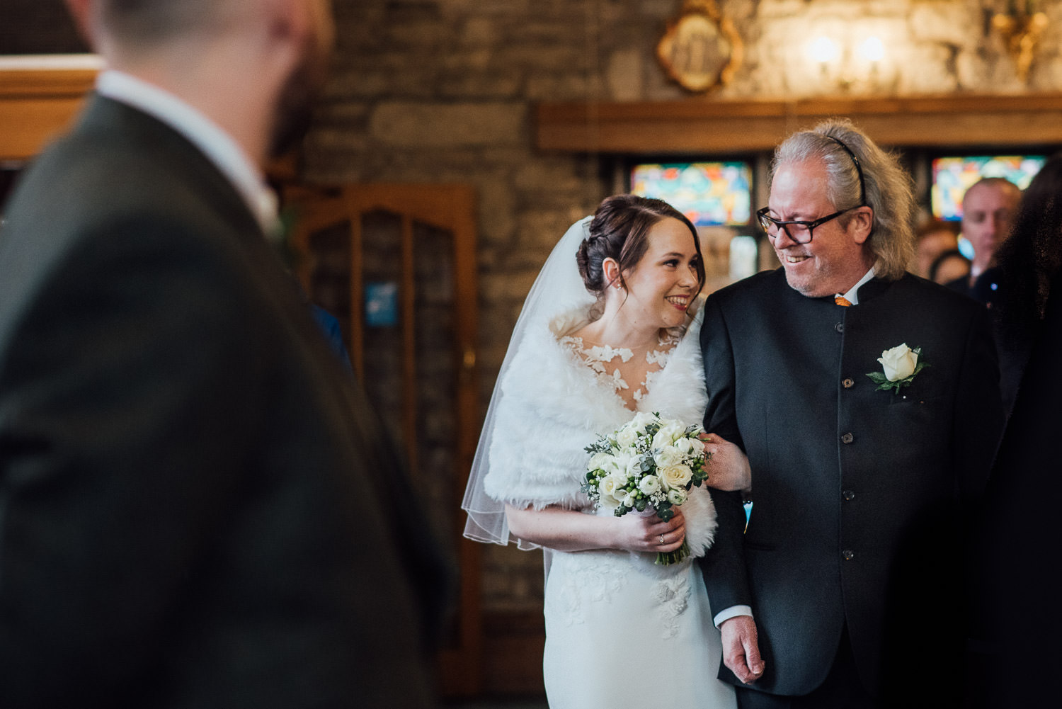 bride smiling at Dad walking down the aisle by bath wedding photographer the shannons photography