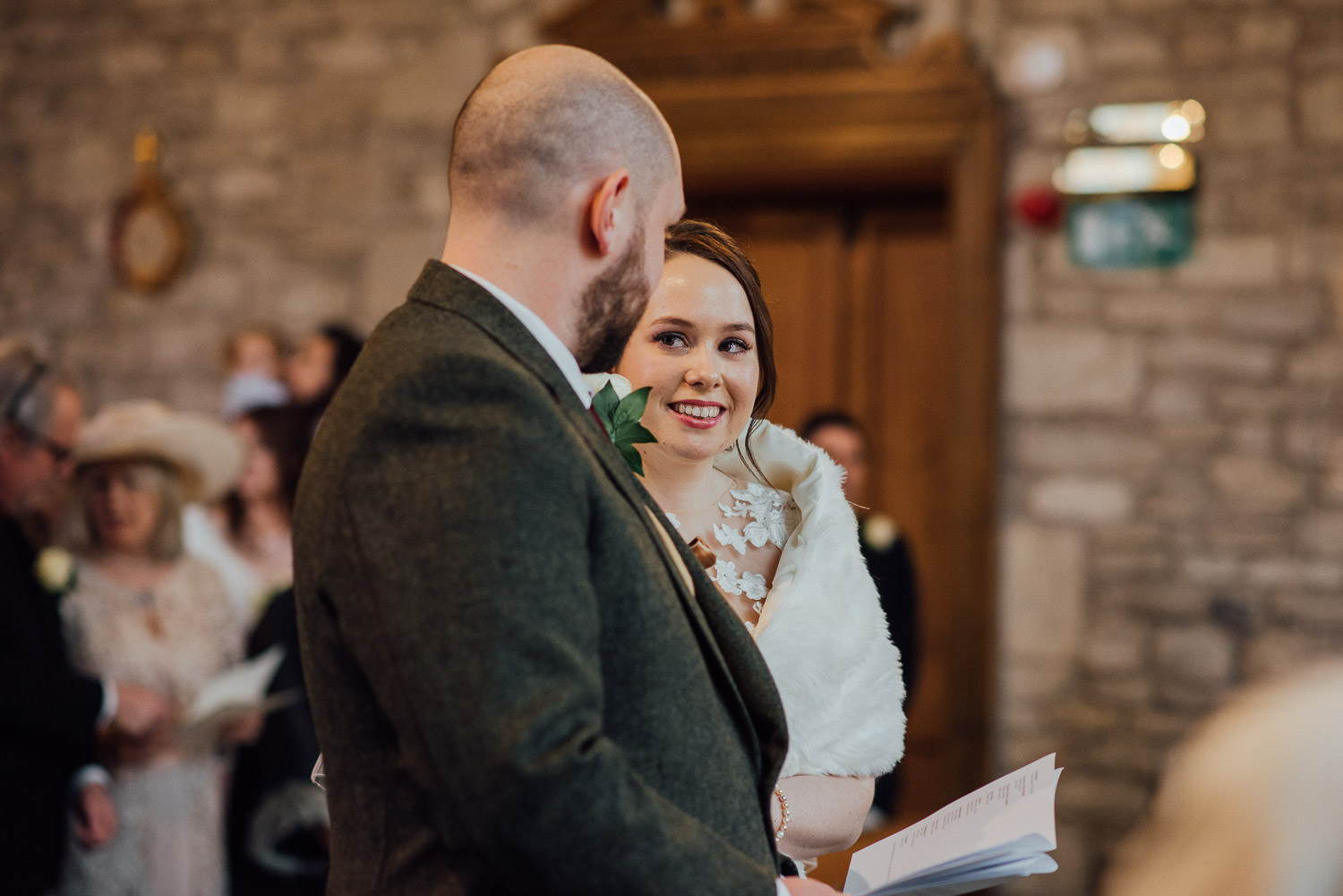 bride smiling at groom in the church ceremony by bath wedding photographer the shannons photography