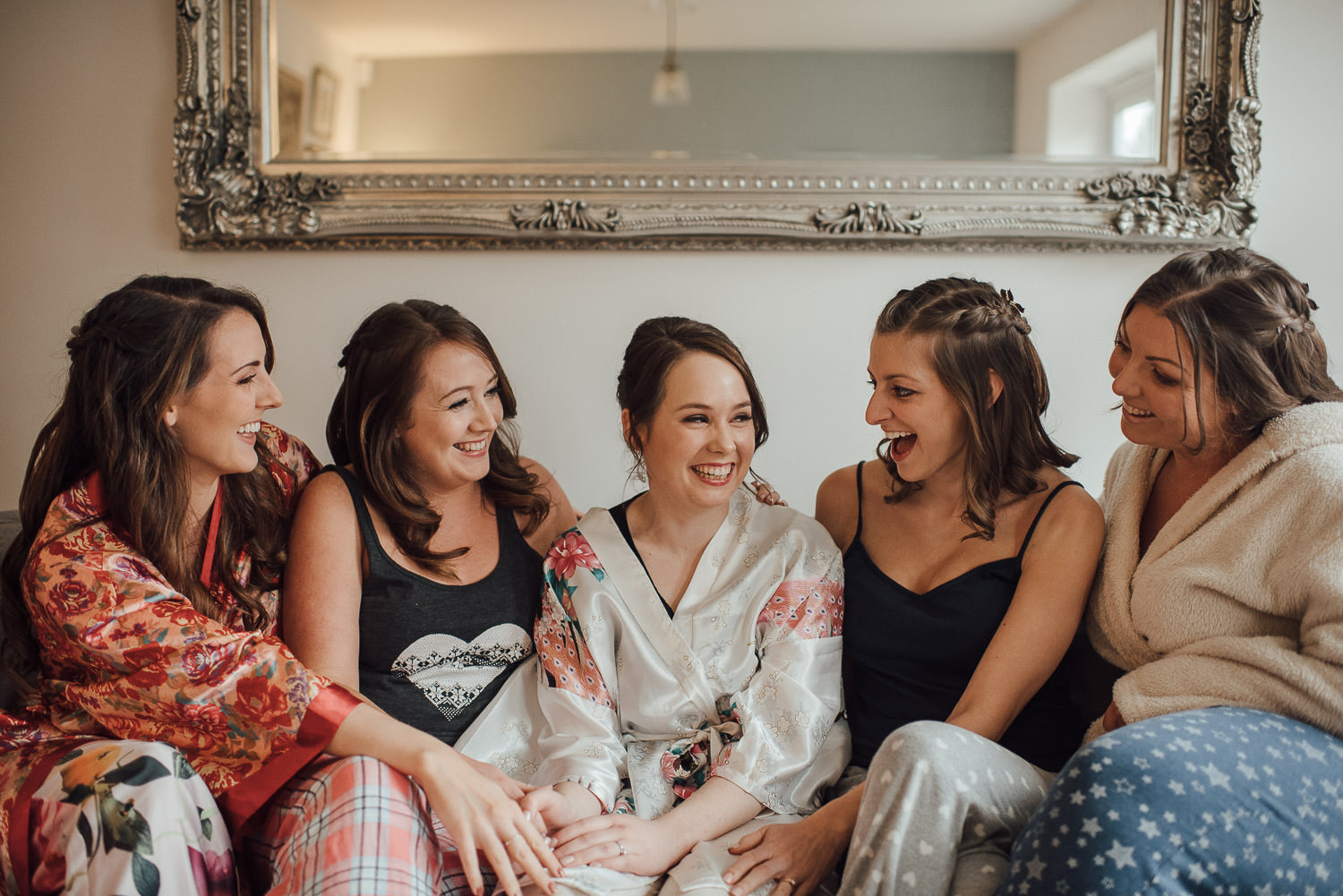 bridesmaids laughing on the sofa with bride by bath wedding photographer the shannons photography