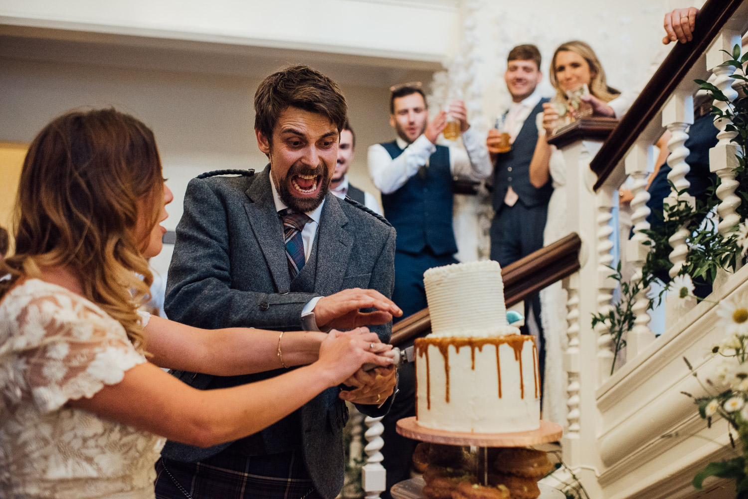 Bride and groom cutting the cake in Barley Wood House Bristol Wedding by bristol wedding photographer the shannons photography