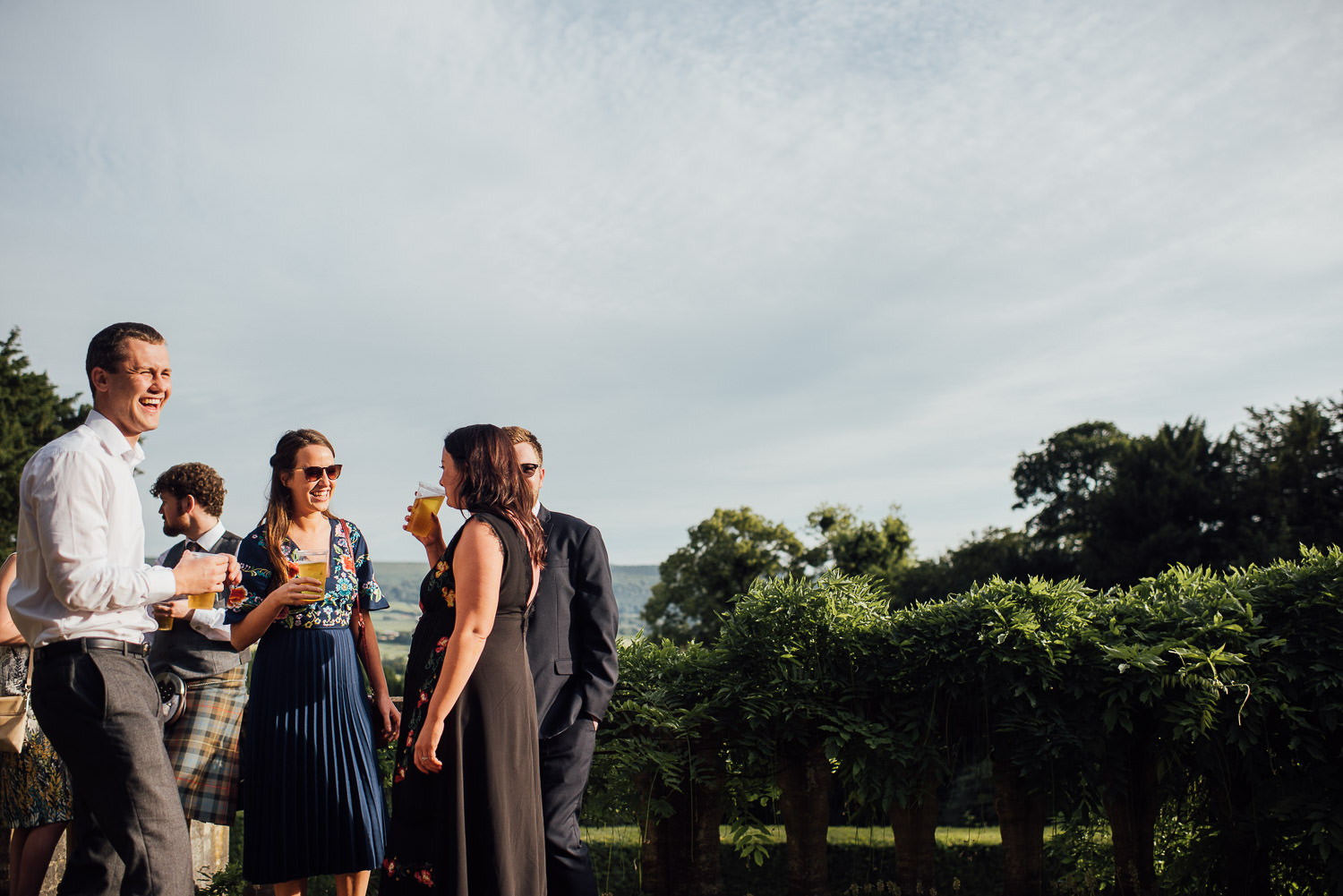 Guests drinking on terrace in Barley Wood House Bristol Wedding by bristol wedding photographer the shannons photography