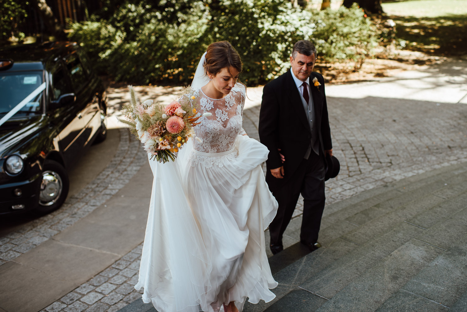 bride arriving wilton's music hall wedding by london wedding photographer the shannons photography