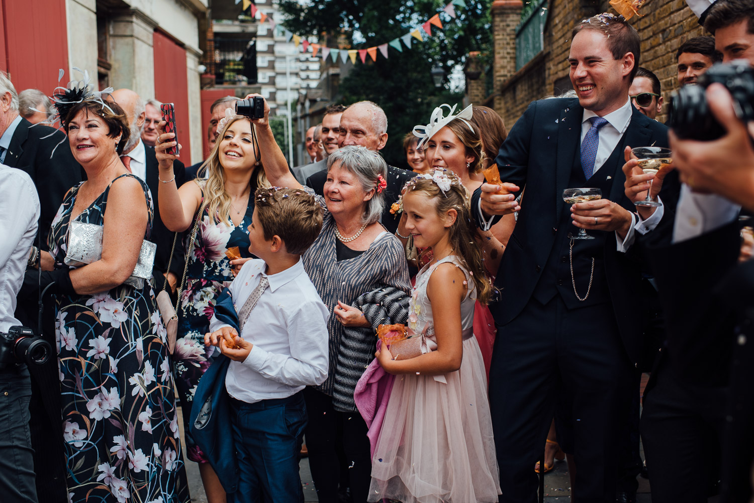 laughing guests wilton's music hall wedding by london wedding photographer the shannons photography