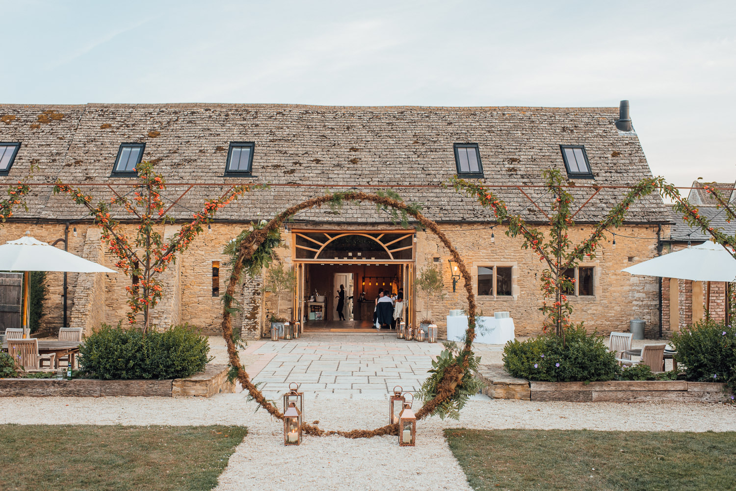 chic floral moongate in oxleaze barn wedding by london wedding photographer the shannons photography