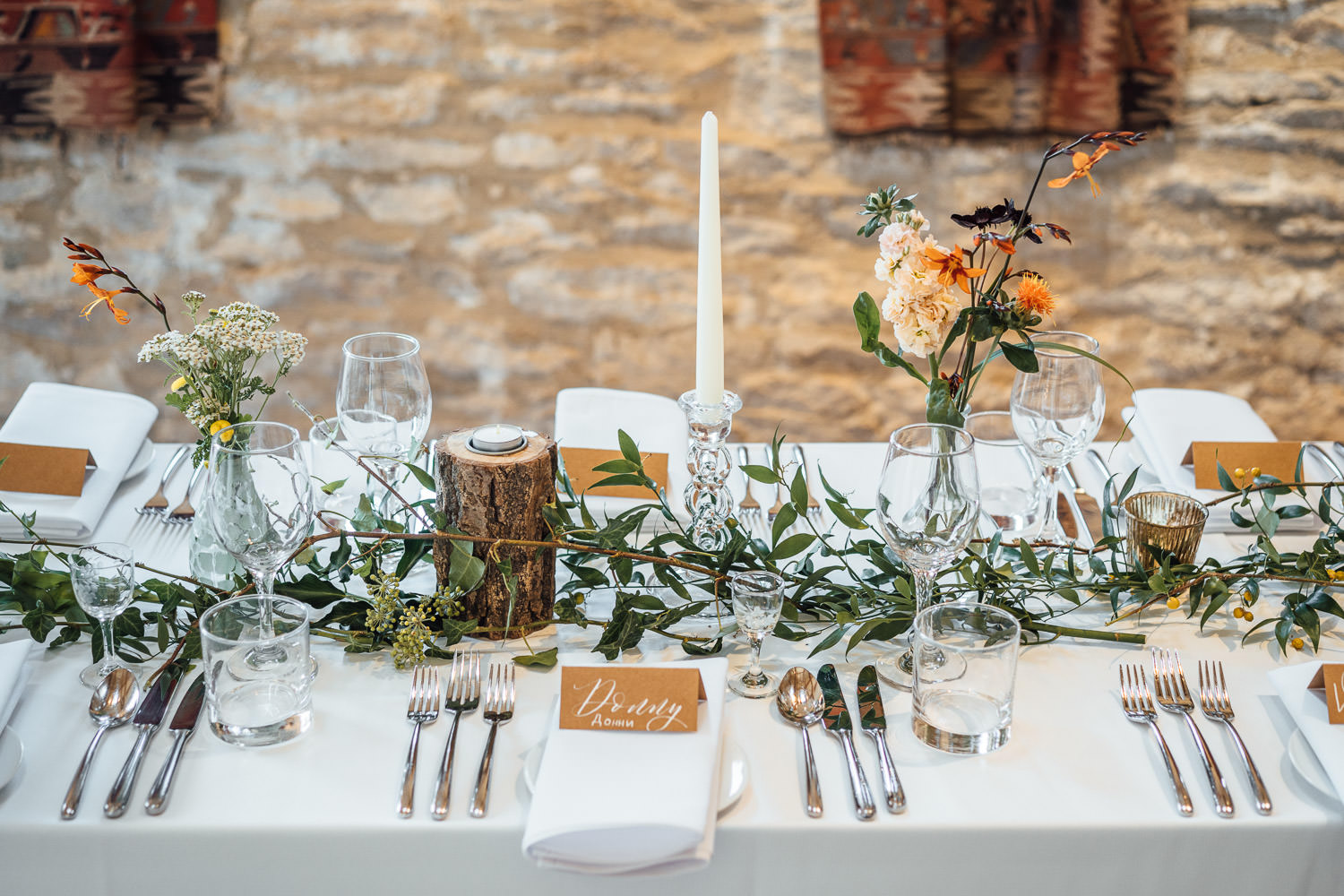 rustic floral table decorations in oxleaze barn wedding