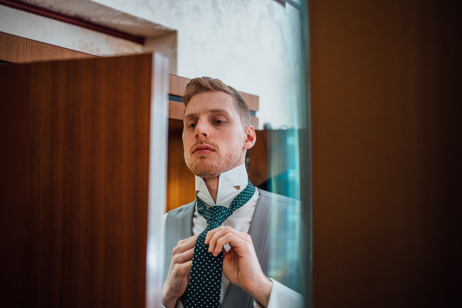 groom getting ready by documentary wedding photographer