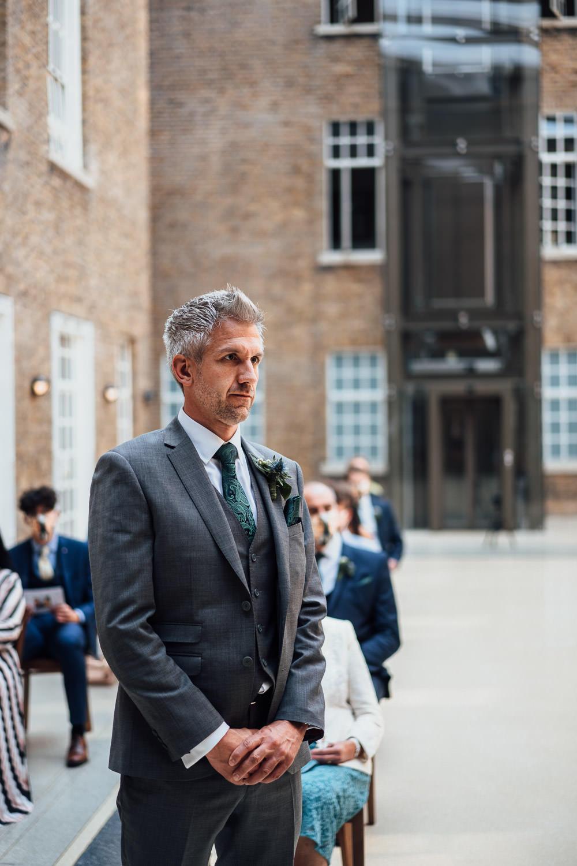 groom waiting in hackney town hall wedding by london wedding photographer